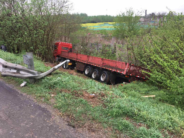 雨天路滑一红色货车失控侧翻冲出高速