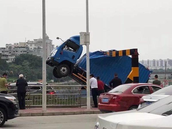 惊险!河源市区一货车被卡住车头悬在空中下不来!