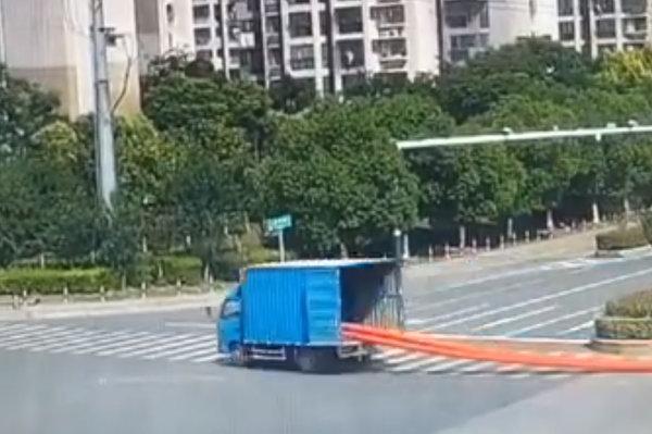 """货车拖100米长塑料管在马路上演""""神龙摆尾""""旁边的电动车很受伤"""