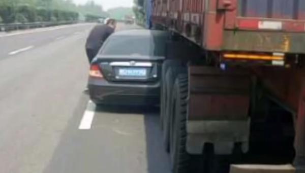 轿车模仿电影情节 想要横穿货车却被卡