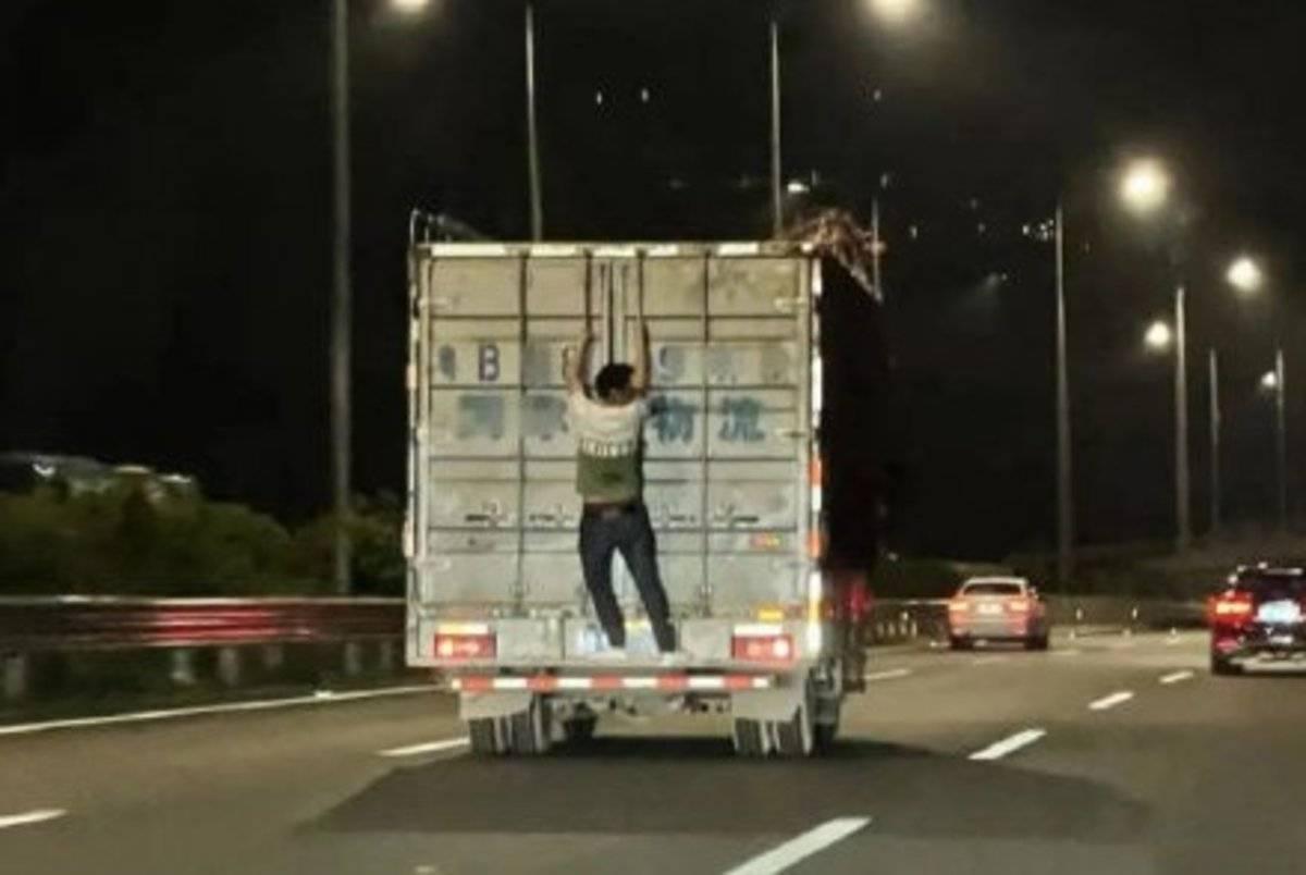 高速上一名醉酒男性扒在货车门上摇摆